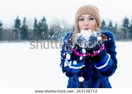 beautiful cute sexy playful happy young woman in a blue coat in the cap playing with snow in the park - stock photo