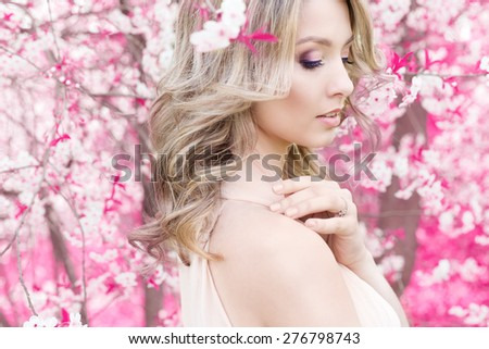 beautiful cute tender young blonde girl in the rose garden in flowering trees in the gentle fabulous colours - stock photo