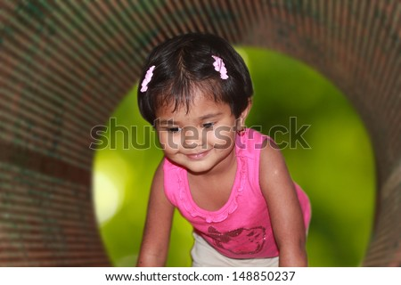 beautiful & cute young girl kid smiling & playing in a park. The photo shows a pretty indian female child having fun and enjoying her time - stock photo