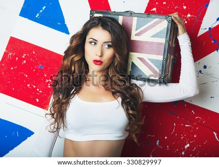 Beautiful Cute young Woman posing with a Suitcase. Young Woman standing with the UK flag in the background. A Trip to England in London, Travel and Study. English language learning concept - stock photo
