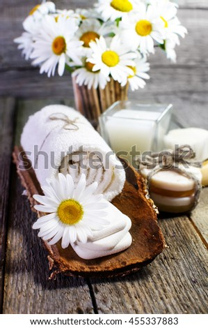 Beautiful daisies, candle, aromatic oils and other spa accessories on wooden surface. - stock photo