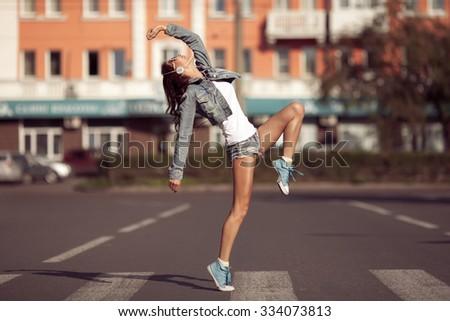 Beautiful dancing girl on a street - stock photo