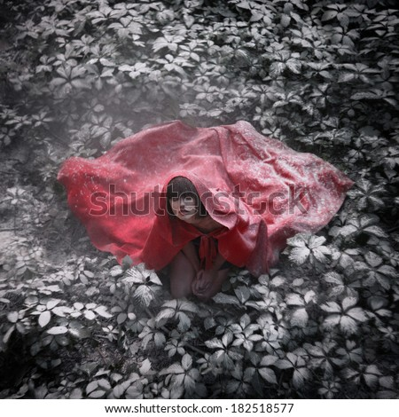 Beautiful dark-haired girl in a red cloak was lost in the wild forest. Little Red Riding Hood story. Fairy tale and legend. Grain added - stock photo