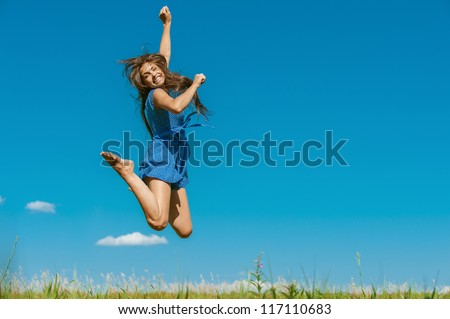 Beautiful dark-haired happy young woman jumping high in air, against background of summer blue sky. - stock photo