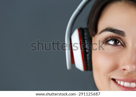 Beautiful dark haired smiling woman wearing headphones and listening music on grey background - stock photo