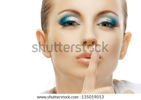 Beautiful dark-haired woman in white T-shirt raised index finger to lips, close-up, isolated on white background. - stock photo