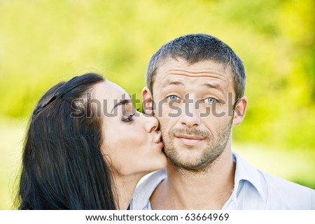 Beautiful dark-haired woman kisses in on cheek young man , against summer solar park. - stock photo