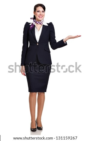 Beautiful dark haired young business woman dressed in a navy suit with a purple scarf and white shirt standing smiling and holding her left hand to the side, isolated on white background - stock photo