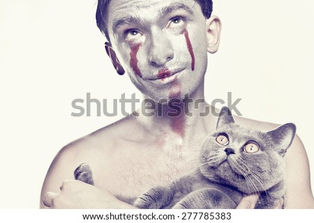 beautiful dark haired young man with silver makeup on his face and cat in  hands - stock photo