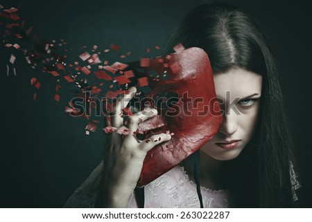 Beautiful dark woman with scattered venetian mask . Surreal and fantasy concept - stock photo