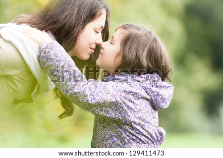 Beautiful daughter and mother looking at each other. Cute kid in jacket hugging mom, green trees in background. Happy smiling people in park. Love between child and parent. Family outdoor activity. - stock photo