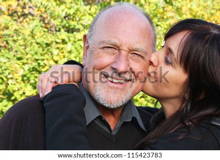 Beautiful daughter kissing her senior father - stock photo