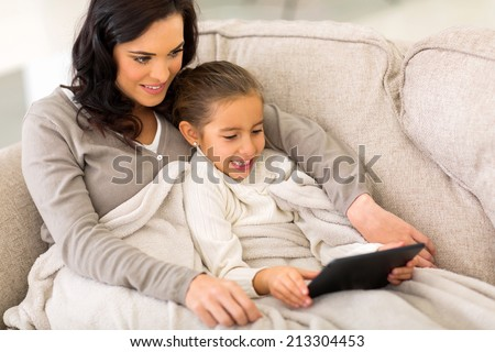 beautiful daughter using tablet computer with her mother on sofa - stock photo