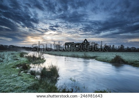 Beautiful dawn landscape of Priory ruins in countryside location - stock photo