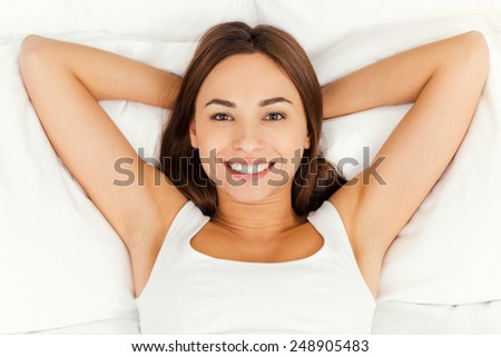 Beautiful day dreamer. Top view of beautiful young woman holding hands behind head while lying in bed and smiling  - stock photo