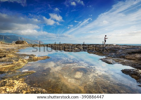 Beautiful day on the north west coast of Oahu in Hawaii, with fisherman along horizon line - stock photo