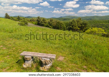 Beautiful day with blue sky and puffy clouds over Blue Ridge Parkway in Southern Virginia with park bench overlooking the scenic highway. - stock photo