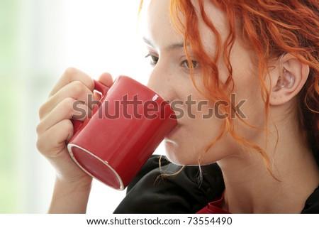 Beautiful deaf woman drinking coffee - stock photo