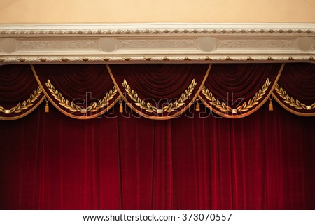 beautiful decorated red curtains in theater top part. - stock photo