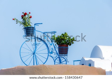 Beautiful decorative bicycle in Oia, Santorini, Greece with pots of flowers against a blue sky - stock photo