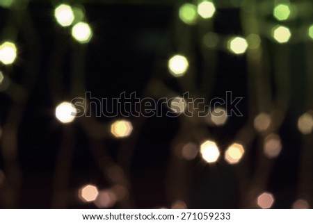Beautiful defocused LED lights filtered bokeh abstract with green-orange-black tone background. - stock photo