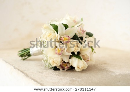 Beautiful delicate wedding bouquet of roses and orchid in pastel colours lying on light holiday background, horizontal picture - stock photo
