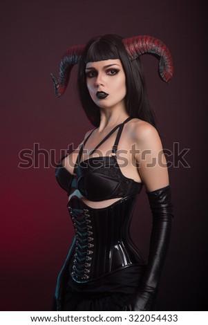 Beautiful demon girl wearing black corset and gloves, Halloween theme  - stock photo