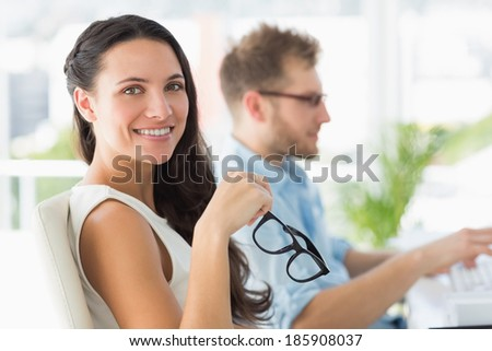 Beautiful designer smiling at camera at desk in creative office - stock photo