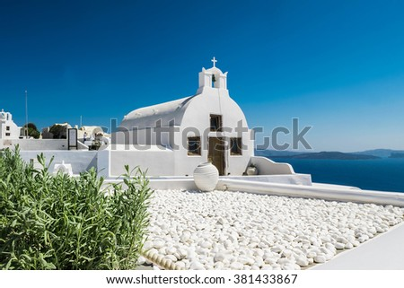 Beautiful details of Santorini island - typical church with white walls, white stones and blue sea Greece - stock photo