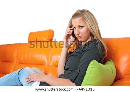 Beautiful disappointed woman speaking on the phone and sitting on the sofa - stock photo