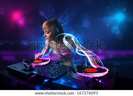 Beautiful disc jockey playing music with electro light effects and lights - stock photo