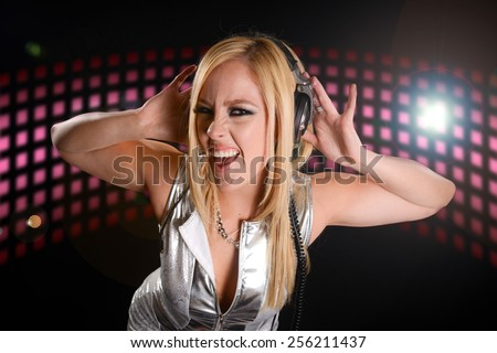 Beautiful DJ Girl Performing with Club Lights in the background - stock photo
