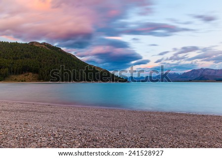 Beautiful dramatic sunset over the incredibly blue lake Tekapo with mountains, Southern Alps, on the horizon. New Zealand - stock photo