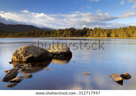 Beautiful early morning light over a tranquil lake. Photographed at Loch Morlich, Cairngorms, Scotland. - stock photo