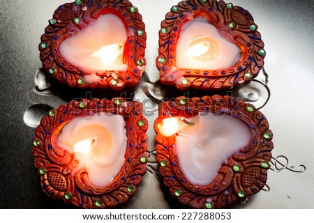 Beautiful earthenware diyas decorated with paint and gemstones on a silver platter. - stock photo