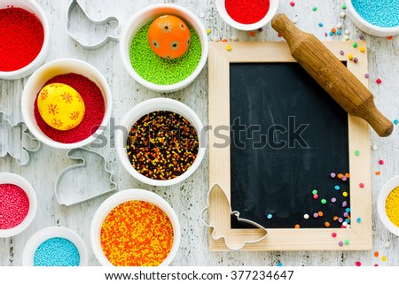 Beautiful Easter food background: colorful eggs, sugar decorations, cookie cutters for the holiday cookies on white background - stock photo