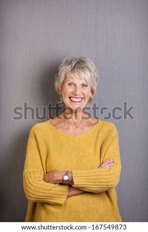 Beautiful elderly lady with a vivacious smile standing with her arms folded grinning happily at the camera in a loose trendy pullover - stock photo