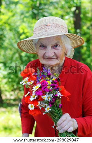 Beautiful elderly woman  holding  bouquet of colourful flower - stock photo
