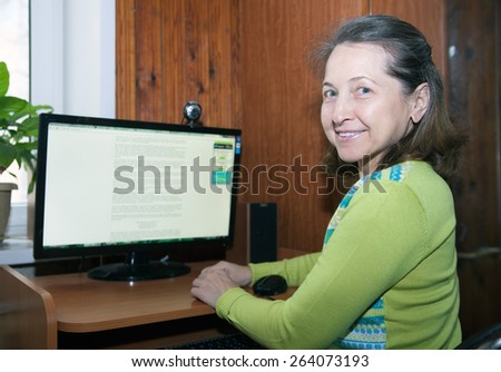 beautiful elderly woman sitting at computer at home.  - stock photo