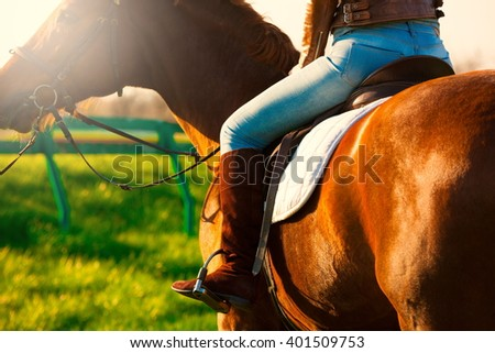 Beautiful elegance back woman cowgirl, riding a horse. Clothed leg in blue jeans, brown leather jacket, boots. Has slim sport body. Portrait nature. People and animals. Equestrian. Close up. - stock photo