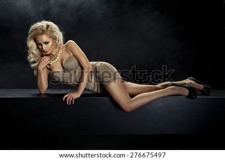 Beautiful elegant blonde woman posing in  lingerie, lying,  - stock photo