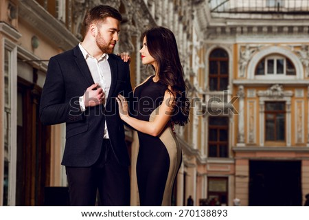 Beautiful elegant brunette with her husband  walking on the ale city streets . Enjoying there time, wearing black classic suit and long cocktail dress. - stock photo