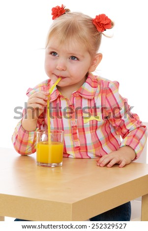 Beautiful elegant girl drinking juice from a glass.Isolated on white background, Lotus Children's Center. - stock photo