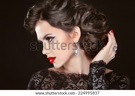 Beautiful elegant girl model with jewelry, makeup and retro hair styling. Isolated on black background. - stock photo