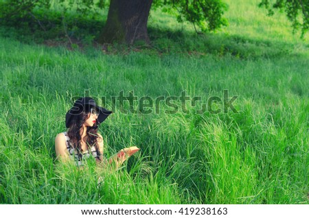 Beautiful elegant girl sitting in grass and reading book on sunny spring day. - stock photo