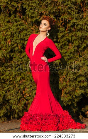 beautiful elegant girl with beautiful makeup and hair in a red evening dress in the Park - stock photo