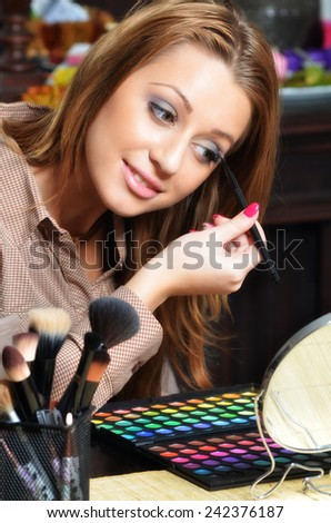Beautiful elegant lady putting make up at home. - stock photo