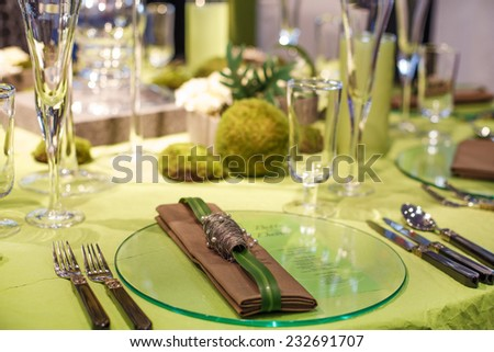 Beautiful elegant table set  for wedding or event party in green and brown with flowers, indoors - stock photo