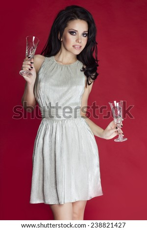 Beautiful elegant woman celebrating, holding champagne glasses. Girl wearing fashionable silver dress, looking at camera. Red background. - stock photo