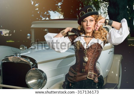Beautiful elegant woman dressed in steampunk style posing over retro car - stock photo